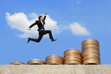 money stacks: business concept - business man run and jump on money stairs with blue sky background, asian male