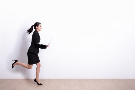 Successful business woman running and hold laptop computer with white wall background, great for your design or text, asian
