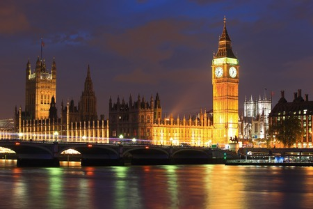 houses of parliament: Big Ben and Houses of Parliament with blur ships on thames river at night, London, United Kingdom, UK Stock Photo