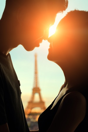 silhouette of romantic lovers with eiffel tower in Paris with sunset photo