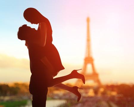 romance: silhueta de amantes românticos com a torre Eiffel em Paris com o por do sol Banco de Imagens