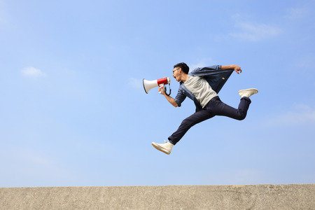 loudspeaker: man jump and shout by megaphone with blue sky background, asian