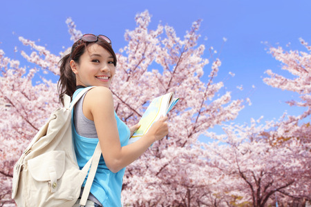 Happy travel woman look map and smile with sakura cherry blossoms tree on vacation while spring, asian