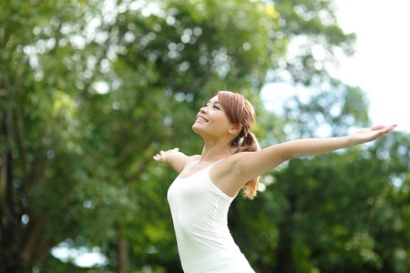 asian natural: Carefree and free cheering woman in the park. girl raising her arms up smiling happy. asian beauty
