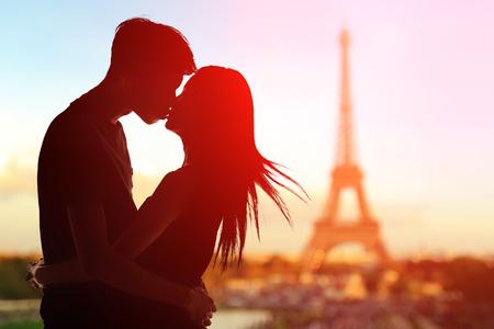 mujer enamorada: silueta de los amantes románticos con la torre Eiffel en París con la puesta del sol