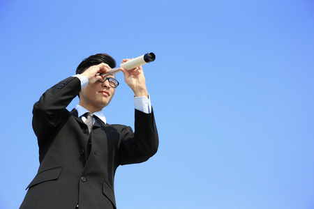 opportunity discovery: Businessman with telescope ( spyglass ) looking forward Prospects for future business with blue sky background, asian Stock Photo