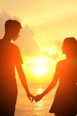 dia y noche: silueta de los amantes rom�nticos abrazo con el mar oc�ano en Maldivas con la puesta del sol Foto de archivo