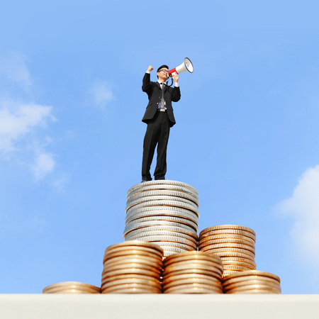 I want be rich - happy business man using megaphone shouting on money stairs with blue sky background, asian photo