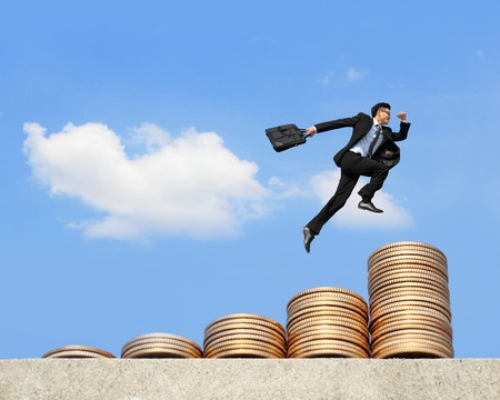 upstairs: business concept - business man run and jump on money stairs with blue sky background, asian male