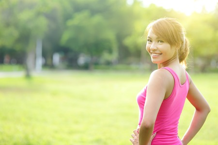 'fit body': Young sport woman stretching and preparing to run in park. asian