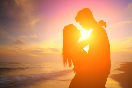 femme romantique: silhouette d'amoureux romantiques c�lin avec l'oc�an de mer et beau coucher de soleil Banque d'images