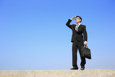 intention: Successful business man purposefully looking away with blue sky, asian male