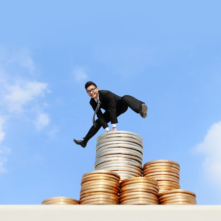 business concept - business man run and jump on money stairs with blue sky background, asian male