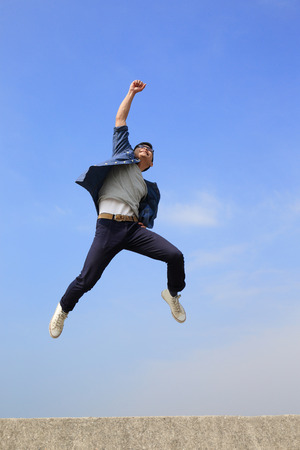 sports winner: Happy College student man run and jump with blue sky background, full length, asian male Stock Photo