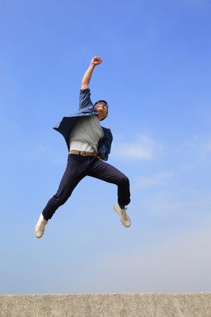 happiness: Hombre feliz del estudiante universitario correr y saltar con fondo de cielo azul, de cuerpo entero, asiático macho