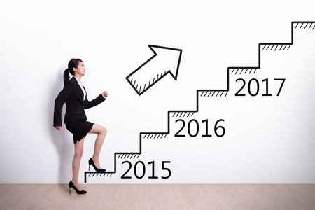 Business woman stepping up on stairs to gain her success in 2015 new year photo