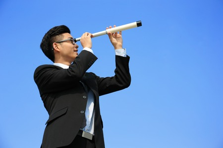 Businessman with telescope ( spyglass ) looking forward Prospects for future business with blue sky background, asian photo