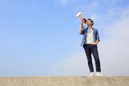 megafono: joven hombre grito por meg�fono con fondo de cielo azul, asi�tico