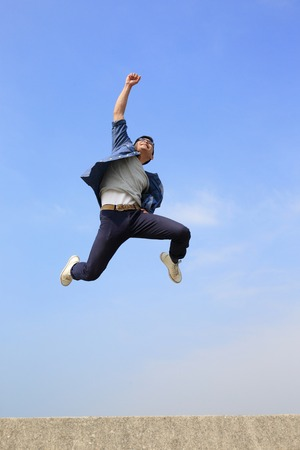 excited man: Happy College student man run and jump with blue sky background, full length, asian male Stock Photo