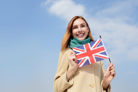 british people: happy young travel woman holding British England flag with sky background, caucasian beauty