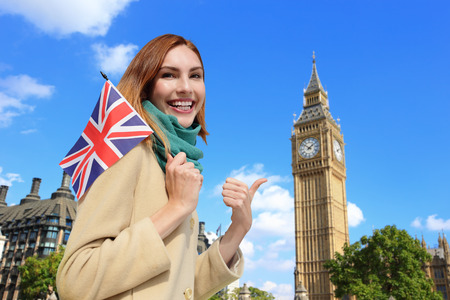 Happy woman travel in London with Big Ben tower, and smile to you, caucasian beauty