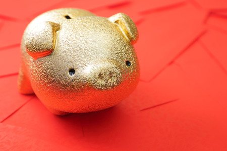 red envelope: Haapy chinese new year - Golden piggy bank with red envelope background Stock Photo