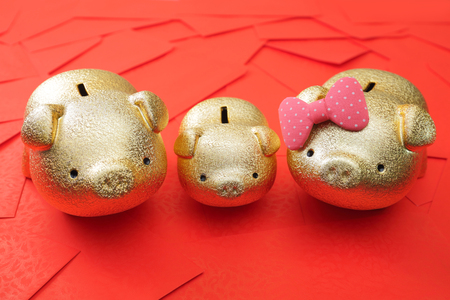 red envelope: Haapy chinese new year - Golden piggy bank family with red envelope background