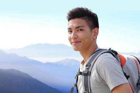 成功した男山ハイカー バックパックを山の上に。アジア