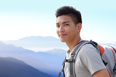 student travel: Successful man mountain hiker with backpack on the top of mountains. asian