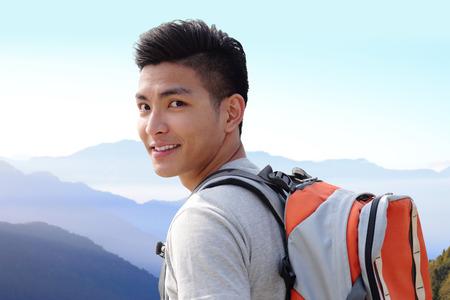 estudiantes: Exitoso hombre excursionista de monta�a con mochila en la cima de las monta�as. asi�tico Foto de archivo