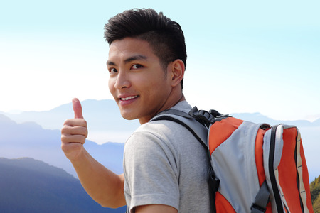 mochila viaje: Exitoso hombre excursionista de monta�a con mochila en la cima de las monta�as. asi�tico Foto de archivo