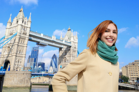 transportation travel: Happy woman travel in London with tower bridge, and smile to you, caucasian beauty Stock Photo