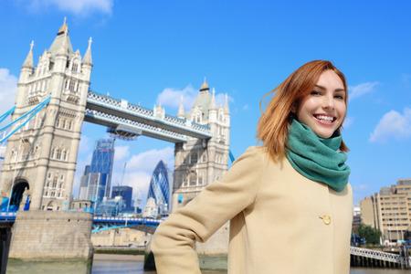 travel: Szczęśliwa kobieta podróży w Londynie z Tower Bridge i uśmiechać się do Ciebie, Kaukaski piękno