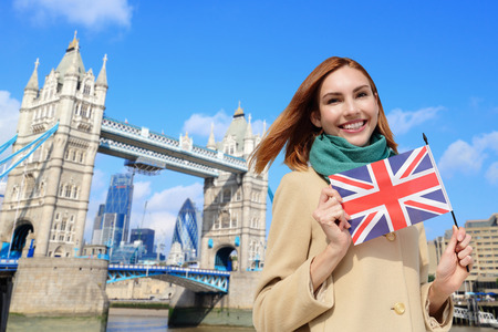 london people: Happy woman travel in London with tower bridge, and smile to you, caucasian beauty Stock Photo