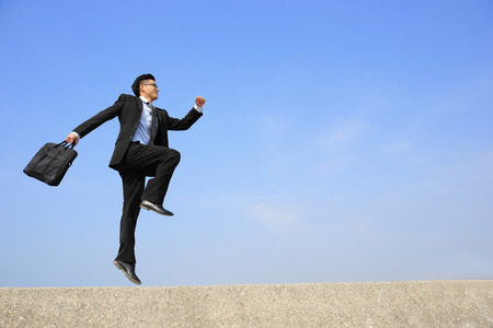 business man jump and run with blue sky background
