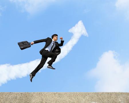 幸せ成功するビジネス人がジャンプして、矢印雲と青い空を背景に実行