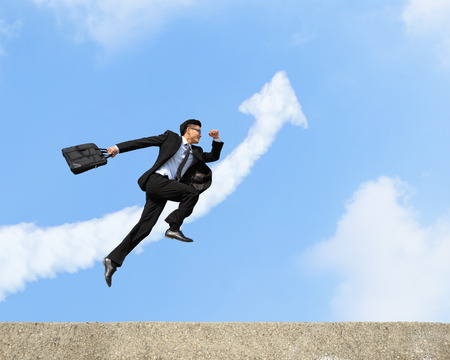 business success: happy successful business man jump and run with arrow cloud and blue sky background Stock Photo