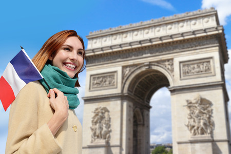 triumphe: Happy woman travel in Paris on background of Arc de Triomphe and holding France flag