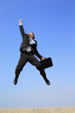 empleados trabajando: exitoso hombre de negocios de salto y correr con fondo de cielo azul Foto de archivo