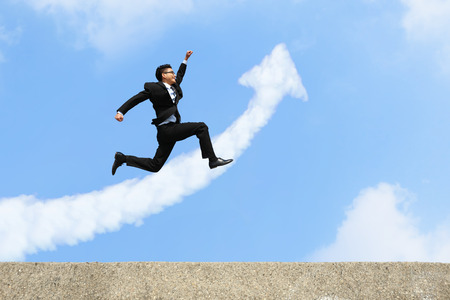 growth arrow: happy successful business man jump and run with arrow cloud and blue sky background Stock Photo
