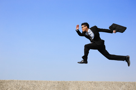 full suit: business man jump and run with blue sky background