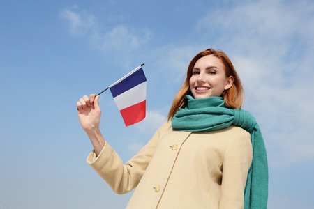 french model: happy young travel woman holding France flag with sky background