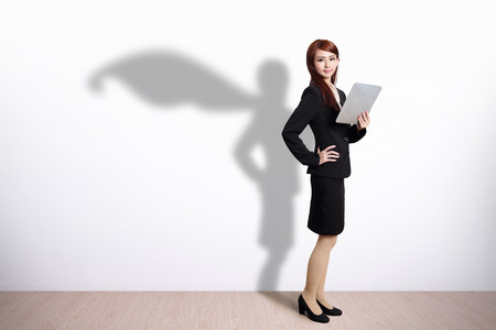 shadow woman: Superhero shadow on Business Woman using digital tablet pc computer with white wall background
