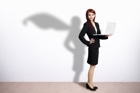 notebook computer: Superhero shadow on Business Woman using laptop computer with white wall background
