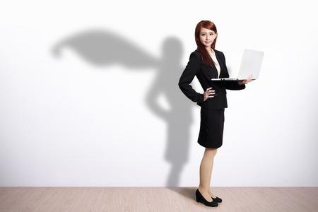 mujer cuerpo entero: Superhero sombra sobre la mujer de negocios usando la computadora port�til con la pared de fondo blanco Foto de archivo