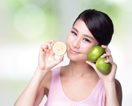 Healthy girl show lemons with smile face photo