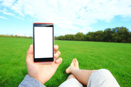 enjoy space: Relax using smart phone and barefoot enjoy nature in the green lawn,  Hyde Park in London, United Kingdom, UK