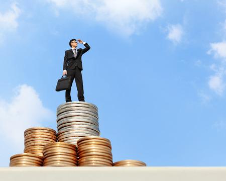 Ik wil rijk worden - Succesvolle zakenman staan op geld met blauwe hemel, Aziatische mannen Stockfoto