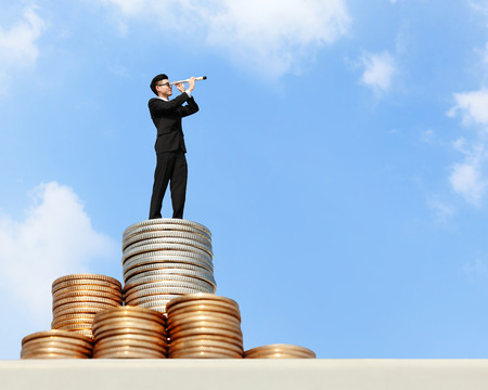 opportunity discovery: I want be rich - Business man stand on money with telescope ( spyglass ) looking forward for future business, asian