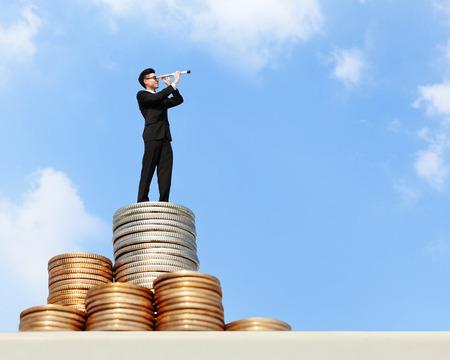 fernrohr: Ich möchte reich sein - Geschäftsmann stehen auf Geld mit Fernrohr (Fernrohr) freut sich für die künftige Geschäftsentwicklung, asiatisch Lizenzfreie Bilder